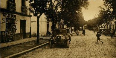 La rue est pavée. Nous sommes au coeur du village face au `Petit Bazar`.